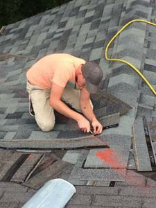 man cutting roof shingles