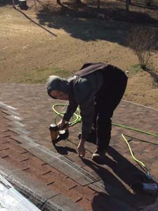 man power nailing roof shingles